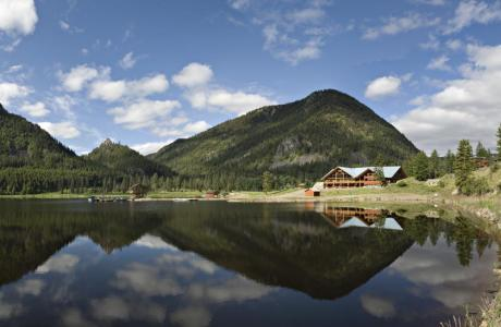 The lake reflects the Pinnacle Dining Hall and surrounding mountains.